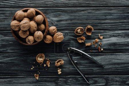 walnuts in wooden bowl and nutcracker on dark wooden background