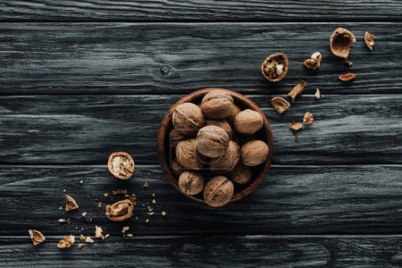 walnuts in wooden bowl with nutshells on dark wooden table