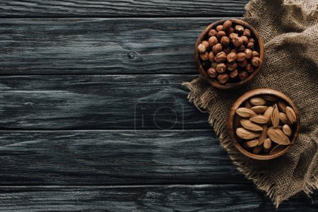 almonds and hazelnuts in wooden bowls with sackcloth on dark wooden surface