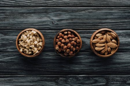 various nuts in three bowls on dark wooden table