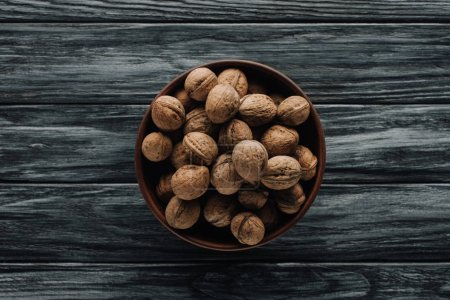 Photo for Walnuts in wooden bowl on dark wooden background - Royalty Free Image