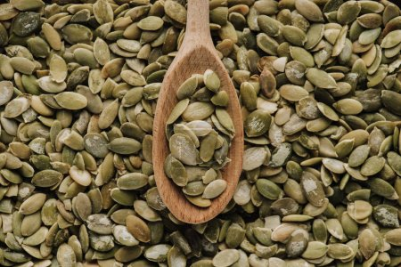 Top view of pumpkin seeds and wooden spoon