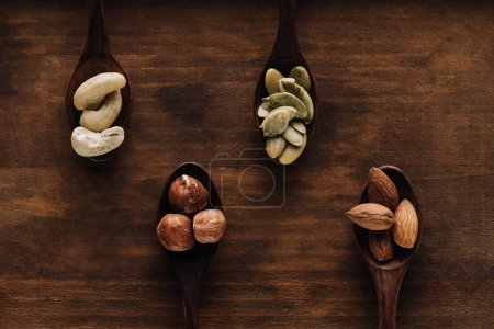 variety of nuts in dark spoons on wooden surface