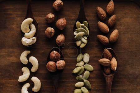 mixed nuts in dark spoons on wooden tabletop