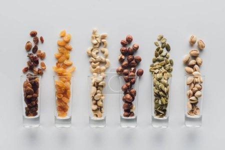 Photo pour Assortiment de délicieuses noix et raisins secs dans des tasses en verre isolées sur fond blanc - image libre de droit