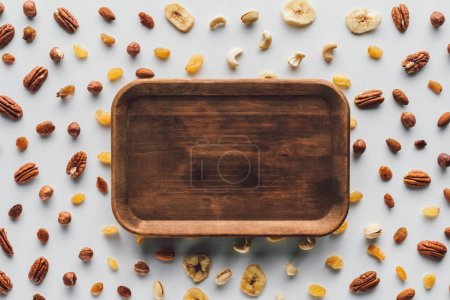 flat lay with dried fruits and nuts with wooden plate in center isolated on white background