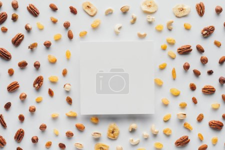flat lay with various dried fruits and nuts with copy space in center isolated on white background