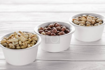Photo for Delicious nuts in ceramic bowls on white wooden tabletop - Royalty Free Image