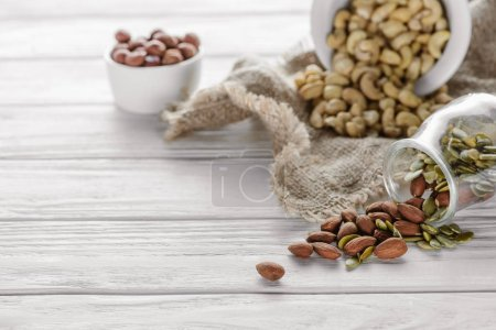 tasty nuts in ceramic and glass bowls on white wooden table