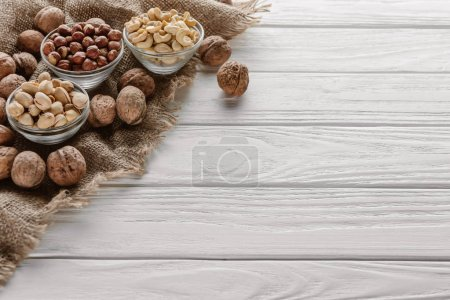 Photo for Assorted nuts in glass bowls on white wooden tabletop - Royalty Free Image