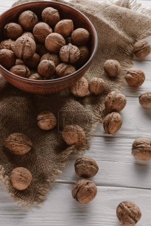 walnuts in wooden bowl with sackcloth on white wooden table