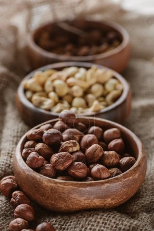 Photo for Various nuts in wooden bowls on sackcloth - Royalty Free Image