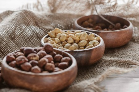 mix of nuts in wooden bowls on sackcloth