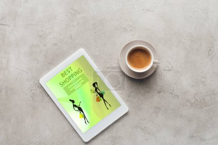 top view of cup of coffee and tablet with best shopping app on screen on concrete surface