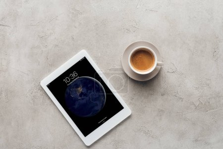 top view of cup of coffee and tablet with ios lockscreen on concrete surface