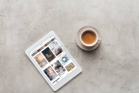top view of cup of coffee and tablet with pinterest website on screen on concrete surface