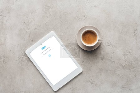top view of cup of coffee and tablet with skype app on screen on concrete surface