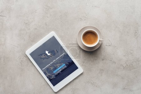 top view of cup of coffee and tablet with tumblr app on screen on concrete surface