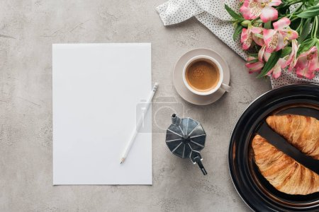top view of cup of coffee with blank paper, croissants and alstroemeria bouquet on concrete surface