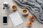 top view of cup of coffee with muffins, blank paper and smartphone with blank screen on concrete surface with knitted wool drapery