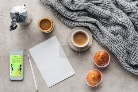 top view of cup of coffee with muffins, blank paper and smartphone with best shopping app on screen on concrete surface with knitted wool drapery