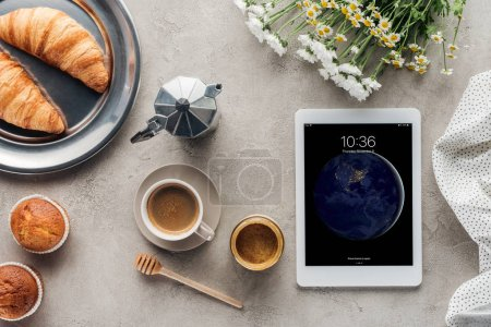 top view of coffee with pastry and tablet with ios lockscreen on concrete surface