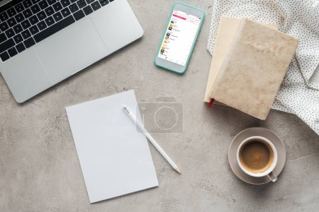 Photo for Top view of coffee with laptop and smartphone with music player app on screen on concrete surface with blank paper - Royalty Free Image