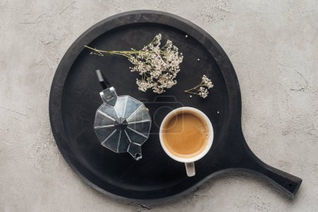 top view of cup of delicious coffee and moka pot with field flowers on concrete surface