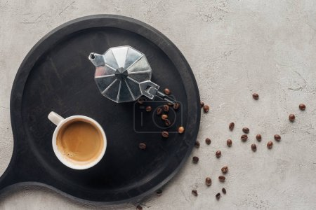 top view of cup of coffee and moka pot on concrete surface