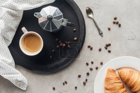 top view of cup of coffee and moka pot on concrete surface with spilled coffee beans and plate of croissants