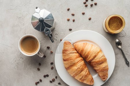 Photo for Top view of cup of delicious coffee with croissants and moka pot on concrete surface with spilled coffee beans - Royalty Free Image