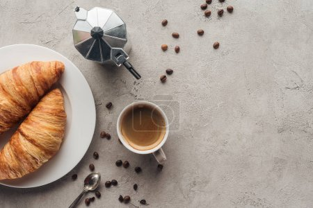 Photo for Top view of cup of coffee with croissants and moka pot on concrete surface with spilled coffee beans - Royalty Free Image