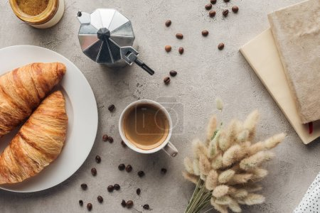 top view of cup of coffee with croissants and moka pot on concrete surface with lagurus ovatus bouquet and book