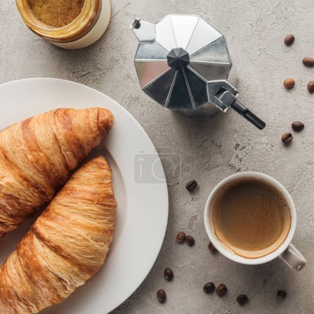 Photo for Top view of cup of coffee with croissants and moka pot on concrete surface - Royalty Free Image