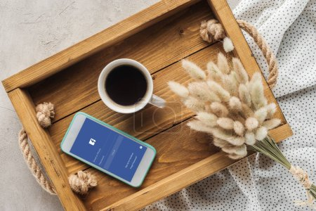 top view of cup of coffee and smartphone with facebook app on screen on tray with lagurus ovatus bouquet on concrete surface