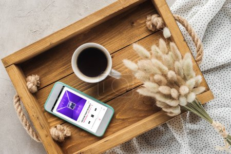 top view of cup of coffee and smartphone with music player playing fall out boy on screen on tray with lagurus ovatus bouquet on concrete surface