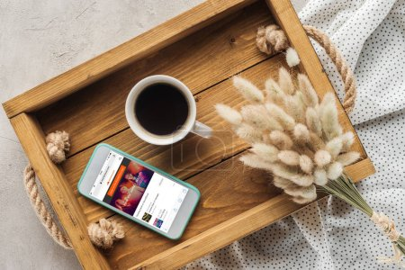 Photo for Top view of cup of coffee and smartphone with soundcloud website on screen on tray with lagurus ovatus bouquet on concrete surface - Royalty Free Image