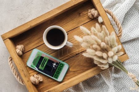 top view of cup of coffee and smartphone with booking website on screen on tray with lagurus ovatus bouquet on concrete surface