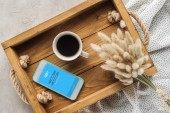 top view of cup of coffee and smartphone with skype app on screen on tray with lagurus ovatus bouquet on concrete surface
