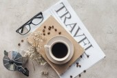 top view of delicious coffee on book and newspaper with travel inscription on concrete surface