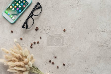 top view of smartphone with ios homescreen with eyeglasses, spilled coffee beans and lagurus ovatus bouquet on concrete surface