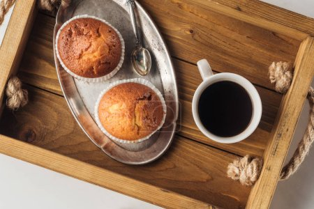 Photo for Top view of cup of coffee with muffins on tray on white - Royalty Free Image