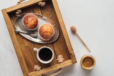 top view of cup of coffee with muffins on tray on white marble