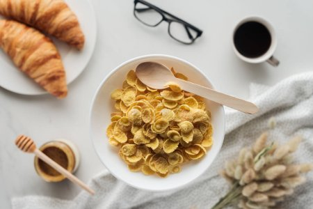 top view of bowl of dry cereal with delicious coffee, croissants and lagurus ovatus bouquet on white