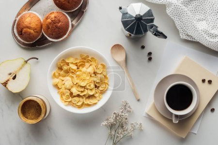 top view of bowl of dry cereal with coffee and muffins on white