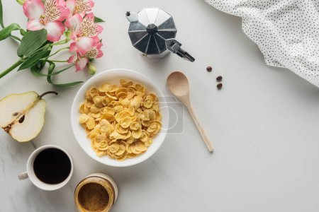 top view of bowl of dry cereal with coffee and alstroemeria bouquet on white