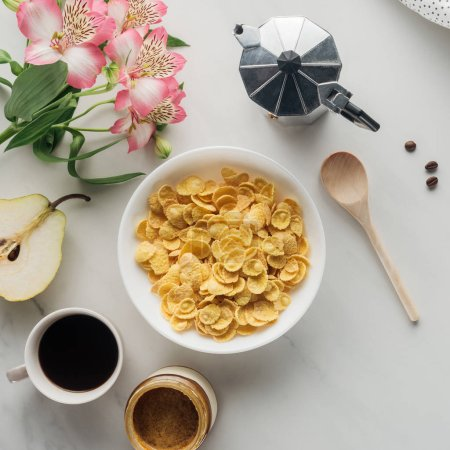 Photo for Top view of bowl of corn flakes with coffee and flowers bouquet on white - Royalty Free Image
