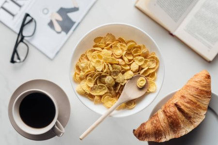 top view of bowl of dry cereal breakfast with cup of coffee and croissant on white surface with newspaper and book