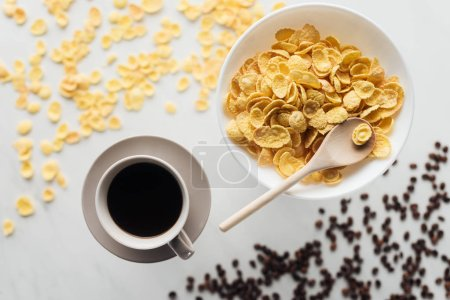 top view of bowl of dry cereal breakfast with cup of coffee on white