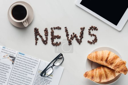 Photo for Top view of coffee with news lettering made of coffee beans, croissants and newspaper with tablet on white marble - Royalty Free Image